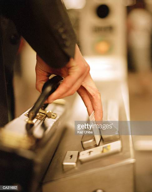 Businessman swiping ticket through subway turnstile, close-up