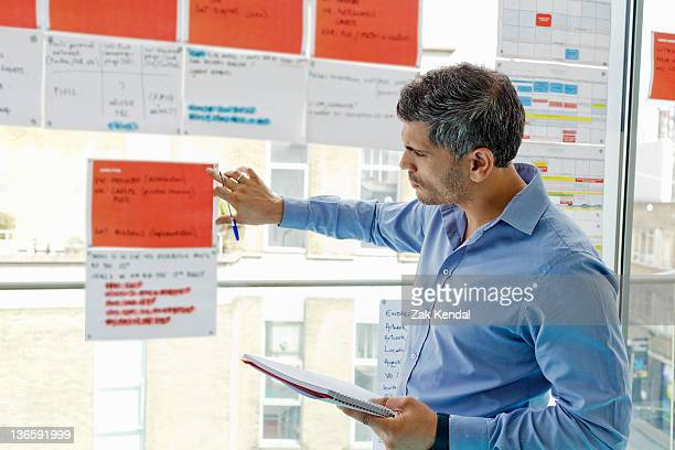 Businessman tacking sheets on window