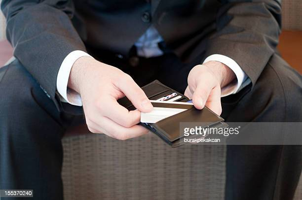 Businessman takes his credit card from the purse