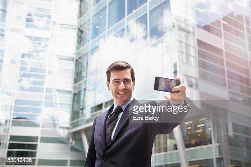 Businessman taking a camera phone photo of himself : Stock Photo