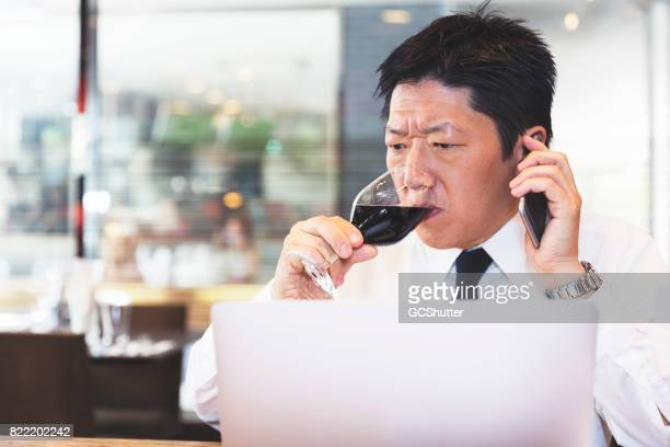 Businessman taking a large drink of his glass of wine while on the phone with a colleague