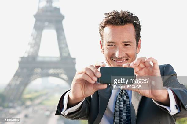 Businessman taking a picture with a mobile phone with the Eiffel Tower in the background, Paris, Ile-de-France, France