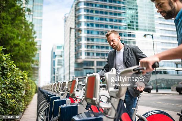 businessman taking a rental bike on the city