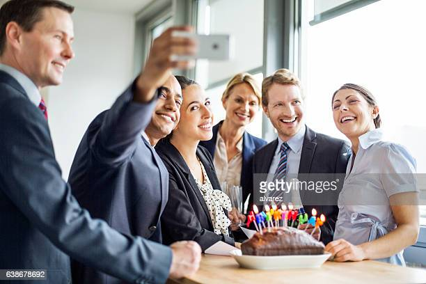Businessman taking a selfie at birthday party in office