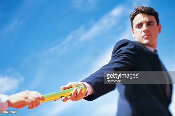 Businessman taking baton from teammate in relay race