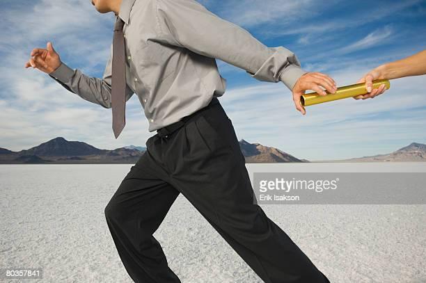 Businessman taking baton in relay race, Salt Flats, Utah, United States