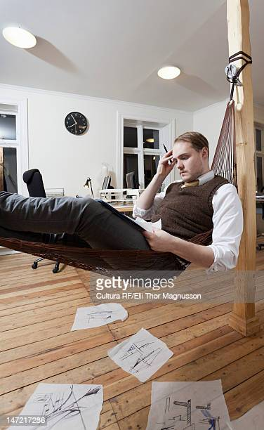 Businessman taking notes in hammock