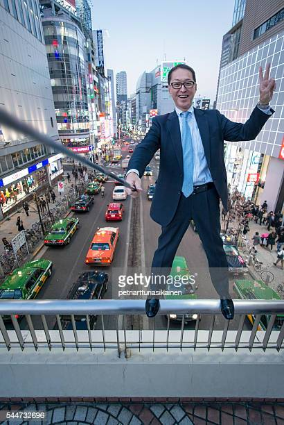 Businessman taking selfie balancing on a handrail.
