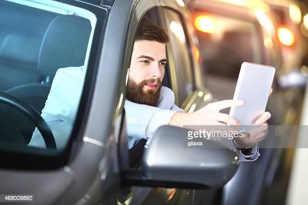 Businessman taking selfie in a car.