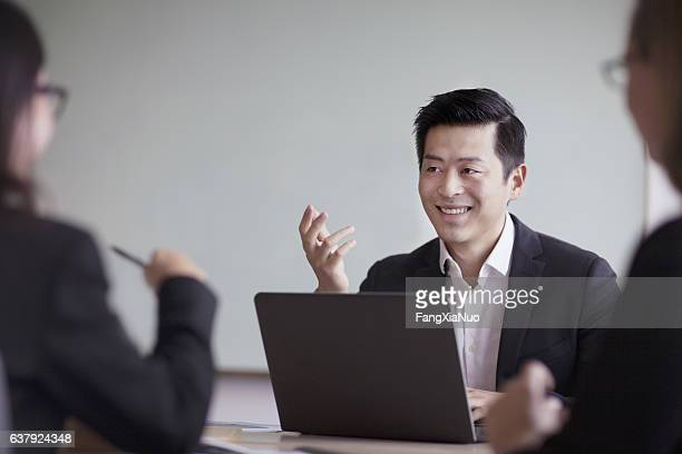 Businessman talking in group office meeting