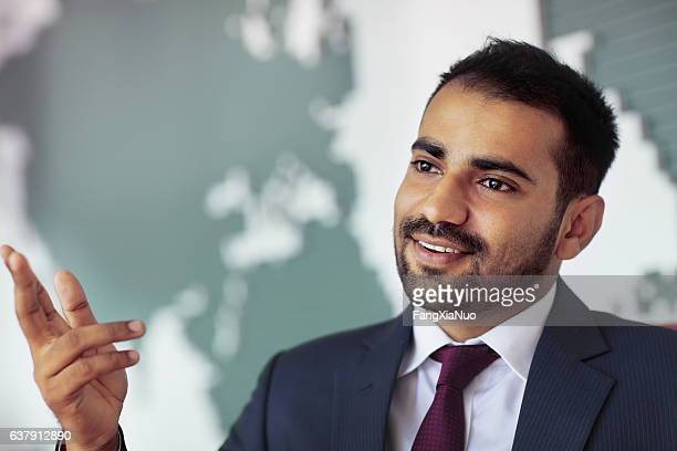 Businessman talking in room with map on wall
