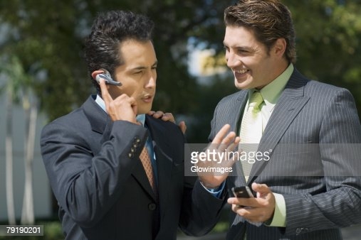 Businessman talking on a hands free device with another businessman standing beside him : Stock Photo