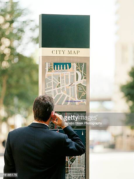 Businessman talking on a mobile phone and checking a city map