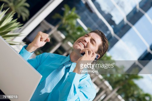 Businessman talking on a mobile phone and looking excited : Stock Photo