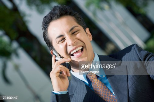 Businessman talking on a mobile phone and smiling : Foto de stock