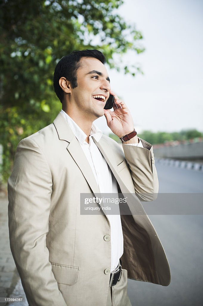 Businessman talking on a mobile phone at roadside : Stock Photo