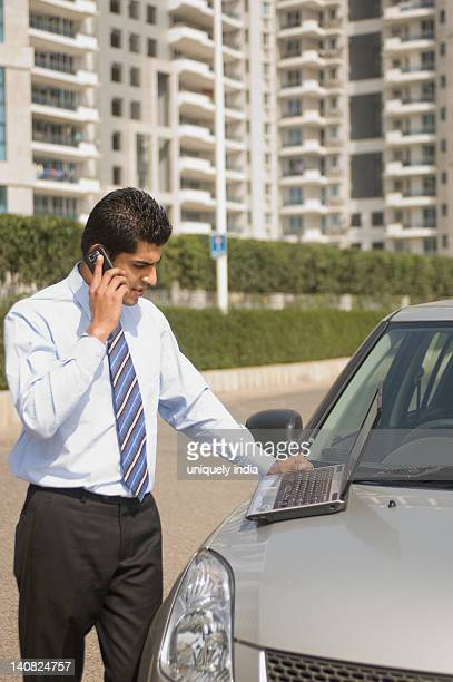 Businessman talking on a mobile phone while using a laptop on car bonnet, Gurgaon, Haryana, India