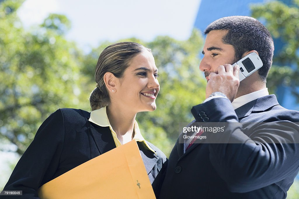 Businessman talking on a mobile phone with a businesswoman smiling beside him : Foto de stock