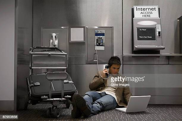 Businessman talking on a pay phone and using a laptop at an airport