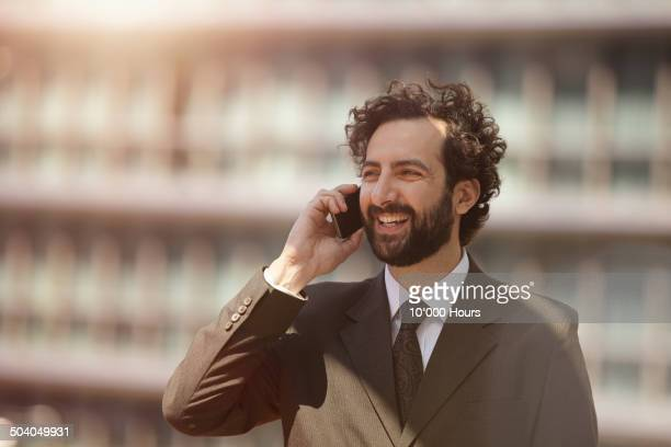A businessman talking on a smart phone in the city
