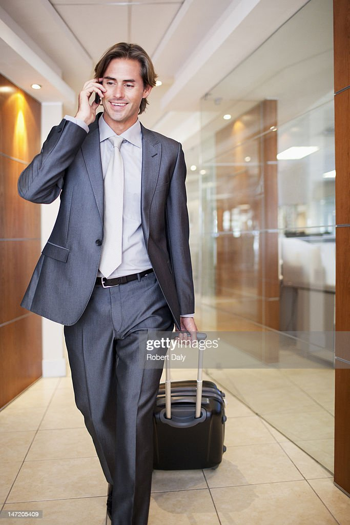 Businessman talking on cell phone and pulling suitcase : Stock Photo