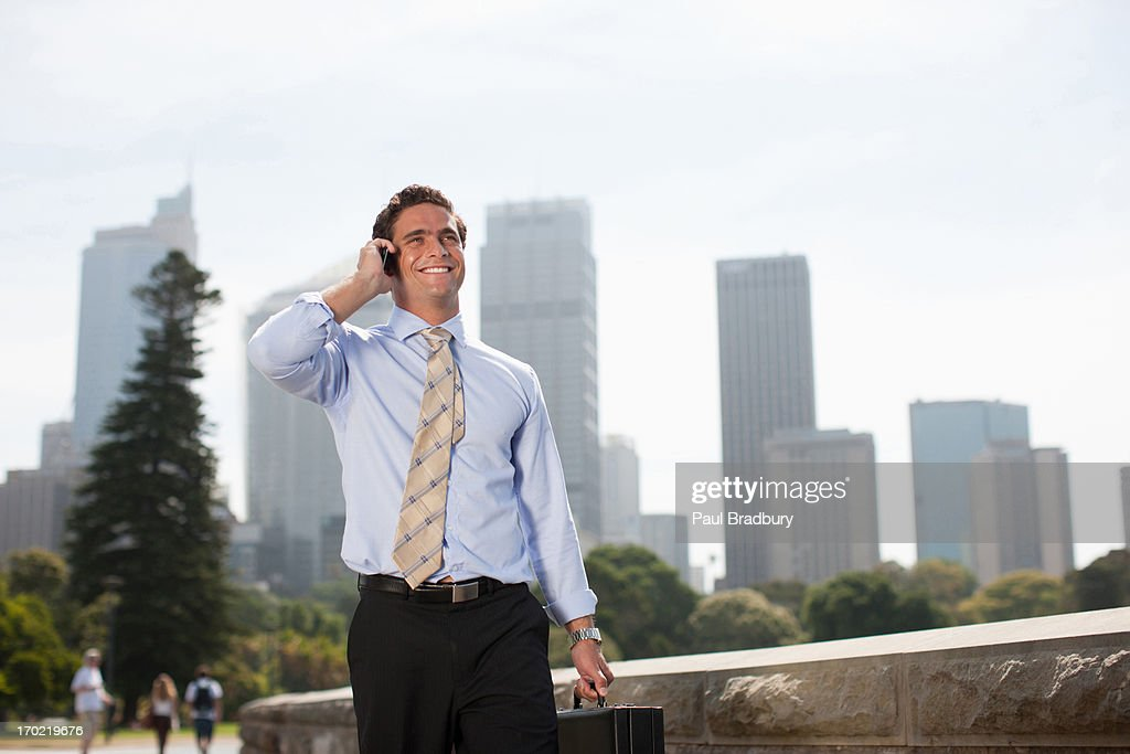 Businessman talking on cell phone at waterfront : Stock Photo