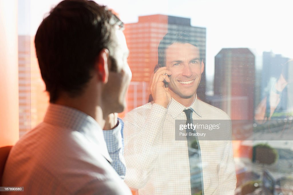 Businessman talking on cell phone at window : Stock Photo
