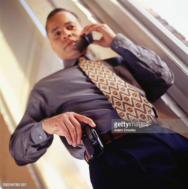Businessman talking on cell phone holding pager, (Low angle view)