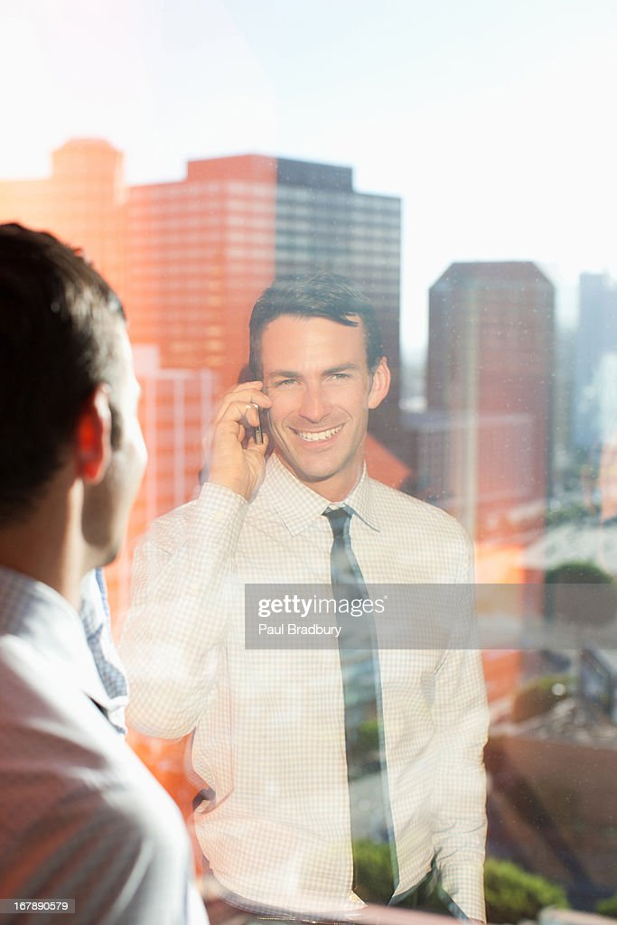 Businessman talking on cell phone in office : Stock Photo