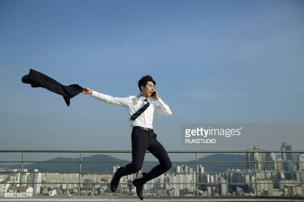 businessman talking on cell phone jumping