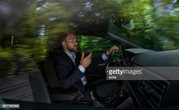 Businessman talking on cell phone while driving