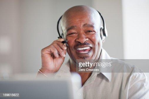 Businessman talking on headset : Stock Photo