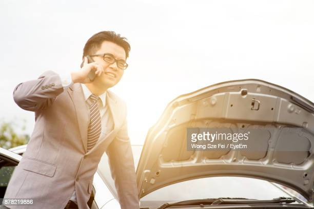 Businessman Talking On Mobile Phone While Standing By Broken Car On Road
