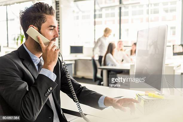 Businessman talking on phone and working in office