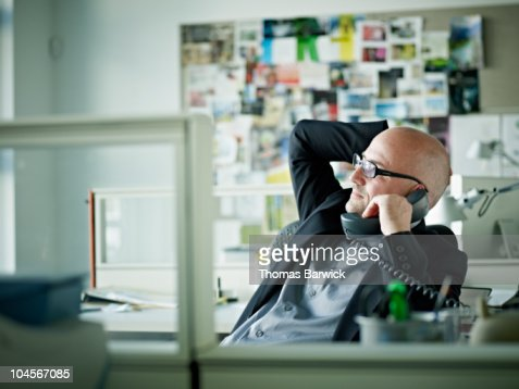 Businessman talking on phone at desk in office : Stock Photo