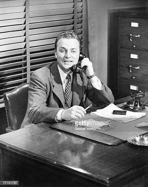Businessman talking on phone at desk (B&W)