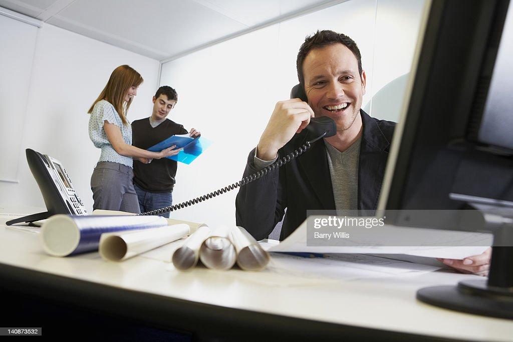 Businessman talking on phone at work