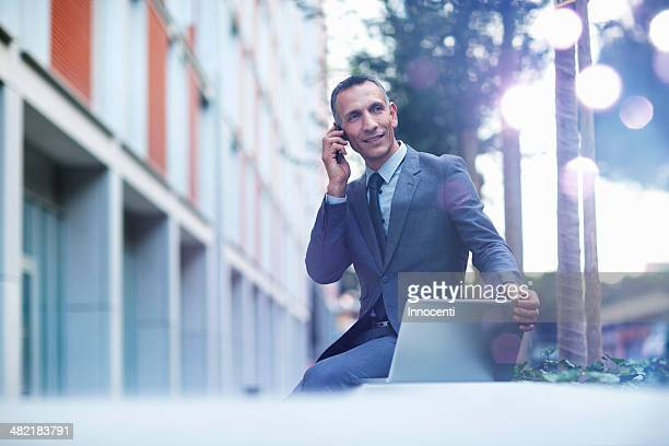 Businessman talking on smartphone and looking at glowing lights