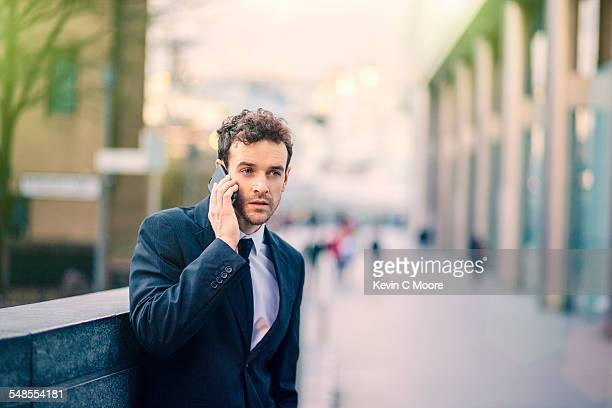 Businessman talking on smartphone on city street