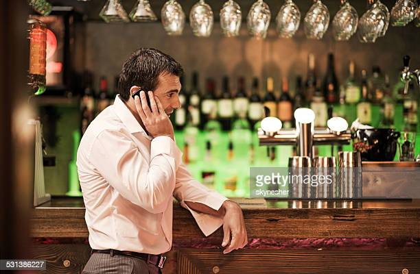 Businessman talking on the cell phone in a bar.