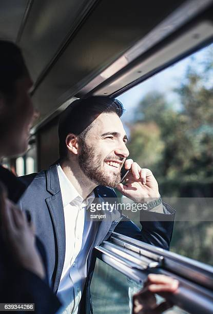 Businessman Talking on The Phone Looking Through Train Window