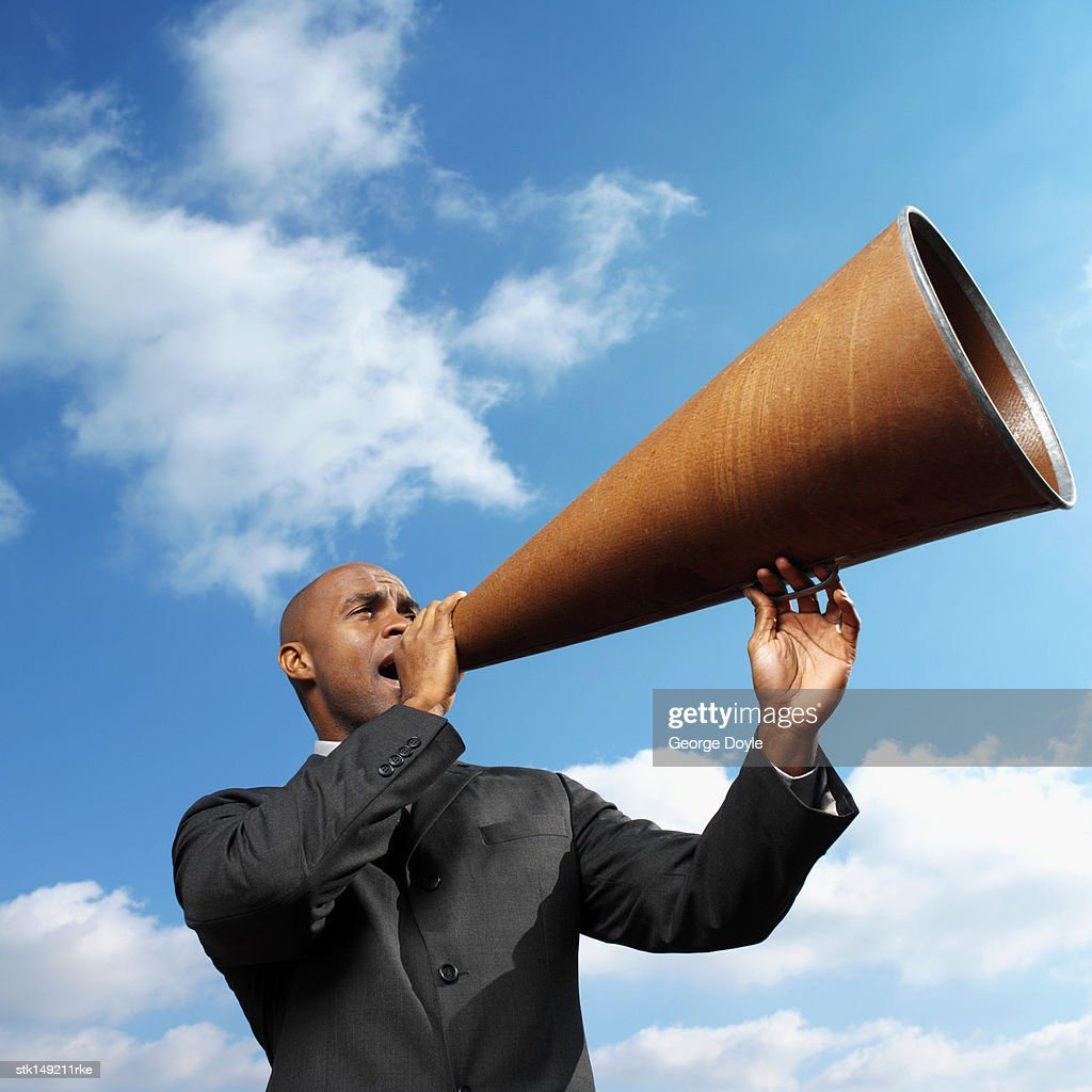businessman talking through megaphone, low angle view : Stock Photo