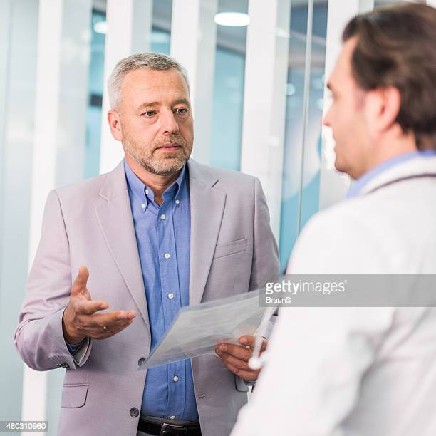 Businessman talking to a doctor about new medical reports.