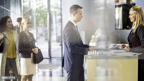 Businessman talking to bank teller at the counter