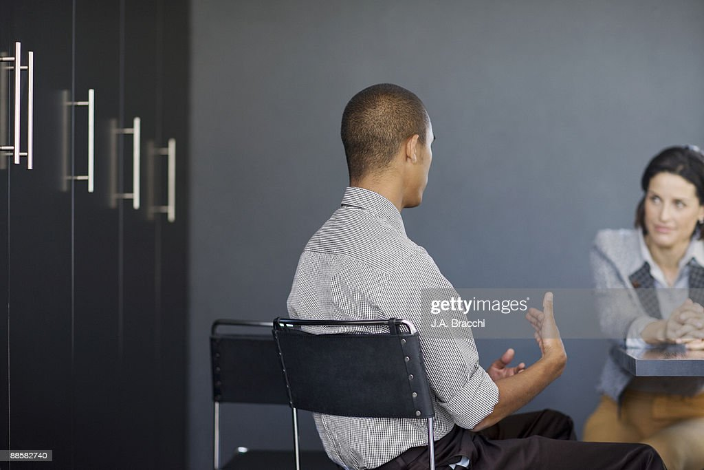 Businessman talking to co-worker in office : Stock Photo