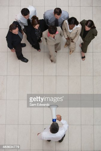 Businessman talking to group of businesspeople with megaphone : Stock Photo