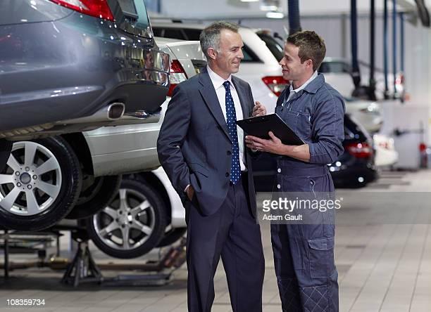 Businessman talking to mechanic in auto repair shop