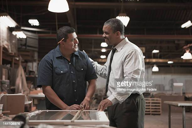 Businessman talking to worker in warehouse