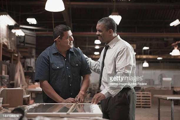 Businessman talking to worker in warehouse