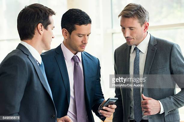 Businessman talking with colleagues, looking at smartphone